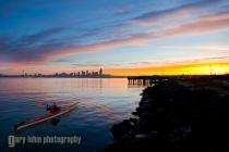 Male sea kayaker in Elliott Bay, Seattle, Washington, at sunrise.