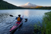 A woman in a sea kayak paddles on Trillium Lake, Oregon, in the Oregon Cascades, with a Mt. Hood backdrop.