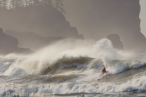 Kayak surfer at First Beach, La Push, surfing winter wave with sea stacks behind. Olympic Coast, Washington State.