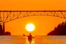 Woman sea kayaker paddles beneath the Deception Pass Bridge.