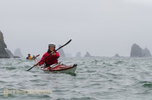 Woman sea kayaker paddles among the sea stack along the Olympic coast, with other kayakers behind, Olympic National Park, Washington State (MR).