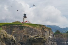 Sea Kayakers paddle beneath the lighthouse on Tatoosh Island near Cape Flattery, the Northwestern-most point in the contiguous US.