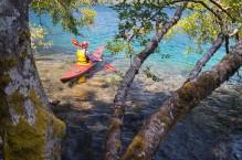 Man paddling sea kayak on Crescent Lake, Olympic National Park, Washington State.