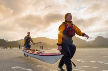 Two women sea kayakers carry a kayak on the beach at Makah Bay, Olympic Coast.