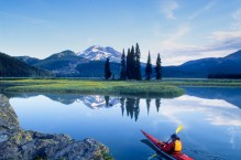 Sea kayaker, wildflowers and Sourth Sister at Sparks Lake, Oregon.