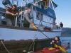 Captain Jim Kyle hands paddle to guest as Ben Kyle looks on, Southeast Alaska.