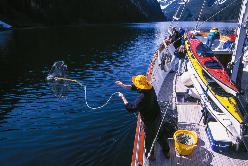 Throwing out shrimp pot from charter yacht Ursa Major at Red Bluff Bay, Baranof Is, AK.
