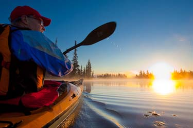 Big Lake, Oregon Kayaker and paddle frame a sunrise.