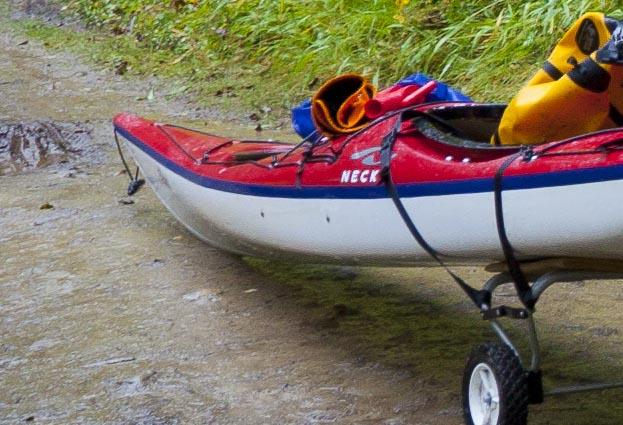 Kayak on cart on Bowron Lake portage showing padding between cart rail and kayak.