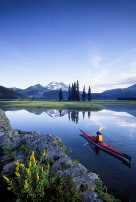 A kayaker paddling into the scene adds the human element at scenic Sparks Lake, OR.