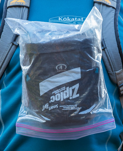 A gallon-size Ziploc bag perfectly covers the Tamrac 3330, shown here clipped to the backpack chest strap.